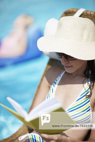 Mid-Adult Woman Reading Book by Pool