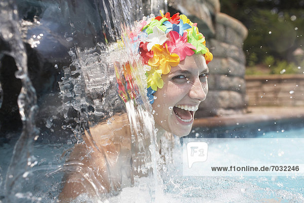 Mid-Adult Woman in Swimcap Laughing Under Waterfall