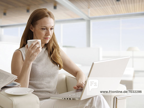 Mid-Adult Woman Using Laptop and Having Coffee