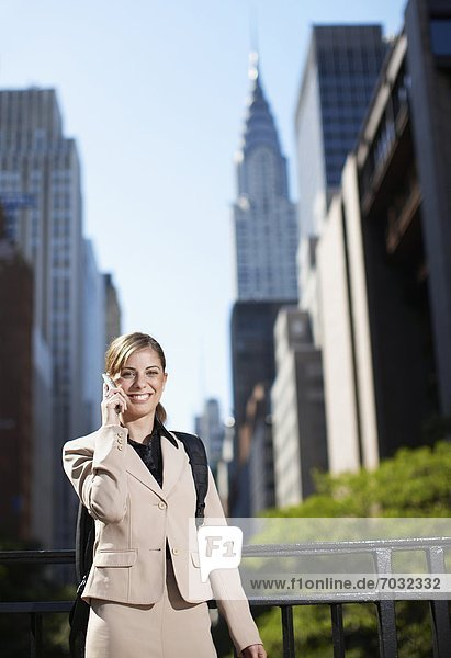 Mid-Adult Businesswoman on Cell Phone by Skyscrapers