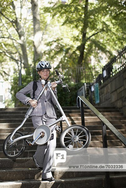 Businesswoman Carrying Bike on Steps
