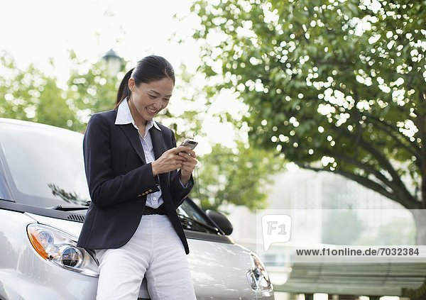 Mid-Adult Woman Text Messaging by Smart Car