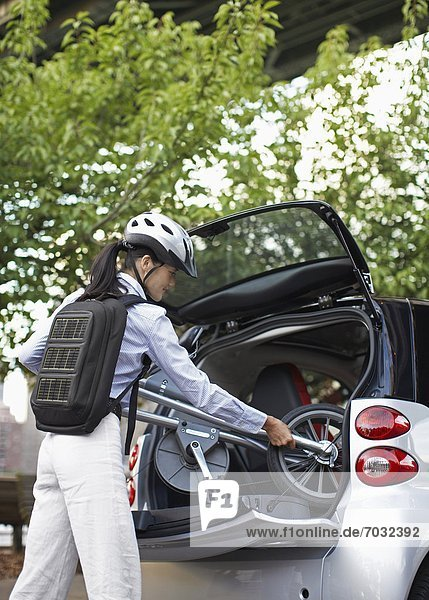 Mid-Adult Woman Putting Bicycle into Car Trunk