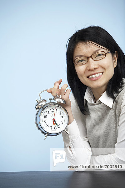 Mid-Adult Businesswoman Holding Alarm Clock