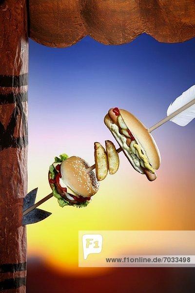 Indianderpfeil in einem Totempfahl mit Burger  Kartoffel Wedges und Hot Dog Indianderpfeil in einem Totempfahl mit Burger, Kartoffel Wedges und Hot Dog