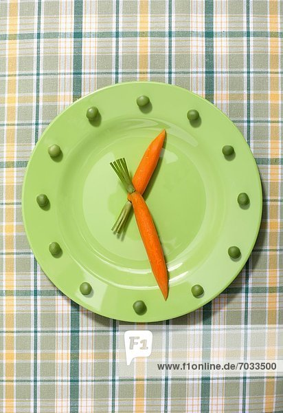 Grüner Teller mit Karotten und Erbsen in Form einer Uhr Grüner Teller mit Karotten und Erbsen in Form einer Uhr