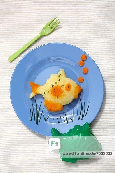 Kinderteller mit Fisch aus Kartoffel- und Karottenbrei Kinderteller mit Fisch aus Kartoffel- und Karottenbrei