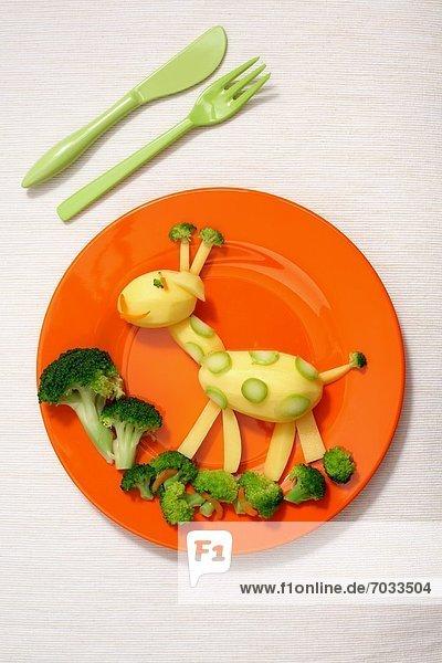 Kinderteller mit Kartoffeln und Brokkoli in Form einer Giraffe Kinderteller mit Kartoffeln und Brokkoli in Form einer Giraffe
