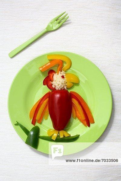 Teller mit Papagei aus Paprikastreifen gelegt Teller mit Papagei aus Paprikastreifen gelegt