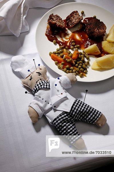 Voodoo-Puppe eines Kochs mit Stecknadeln auf gedecktem Tisch neben dem Essen Voodoo-Puppe eines Kochs mit Stecknadeln auf gedecktem Tisch neben dem Essen
