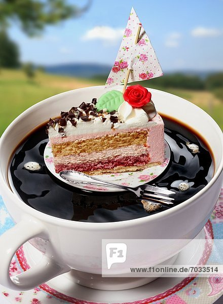 Tortenstück mit Segel und Kuchengabel treiben in einer Kaffeetasse Tortenstück mit Segel und Kuchengabel treiben in einer Kaffeetasse