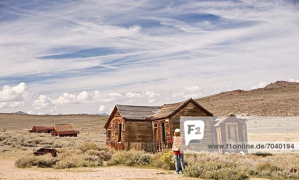 A woman photographer shoots the ruins of an old California ghost town