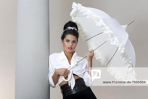 Junge Frau mit Hochsteckfrisur  weißem Schirm und weißem Hemd