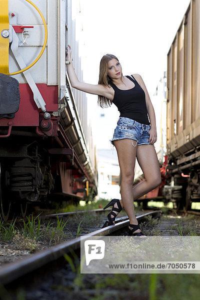 Junge Frau mit schwarzem Top  Jeanshotpants und hohen Schuhen posiert zwischen Güterwaggons