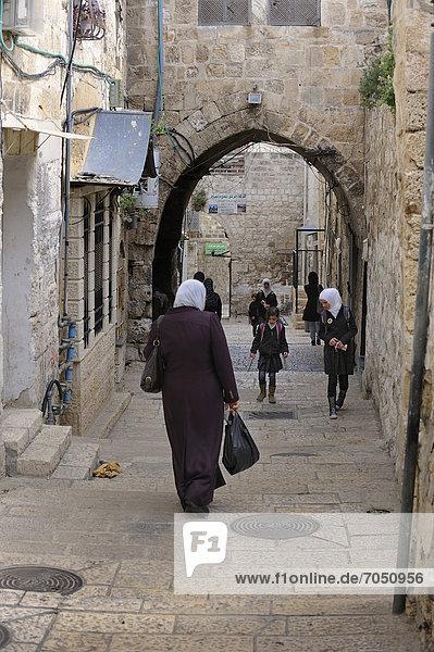 Gasse mit einer palästinensischen Frau und Schüler mit Kopftuch  im Arabischen Viertel in Jerusalem  Israel  Vorderasien  Naher Osten
