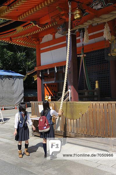 Schüler in Uniform läuten an der Schreinglocke  um die Geister auf sich aufmerksam zu machen  Yasaka-Schrein  Maruyama Park  Kyoto  Japan  Ostasien  Asien