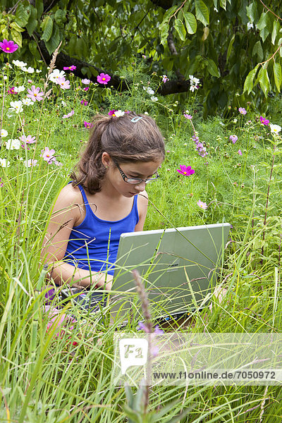 Mädchen  11 Jahre  mit einem Laptop  Notebook  inmitten einer Blumenwiese in freier Natur