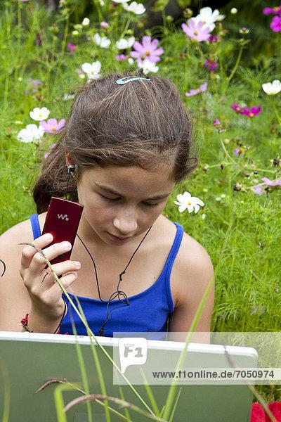 Mädchen  11 Jahre  mit einem Laptop  Notebook hört Musik inmitten einer Blumenwiese in freier Natur