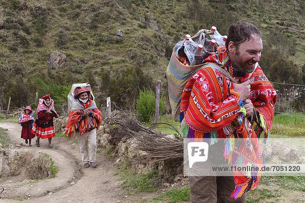 Tourist in traditionellem Poncho der Quechua Indios hilft Einheimischen beim Tragen des Wocheneinkaufs  Anden  bei Machu Picchu  Cusco  Peru  Südamerika