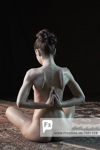 Junge Frau sitzend  Rückenansicht  die Hände am Rücken gegeneinander gepresst  nackt  Yoga-Pose
