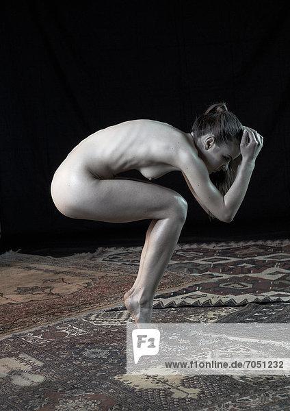 Junge Frau stehend in der Hocke  auf Zehenspitzen  nackt  Yoga-Pose Junge Frau stehend in der Hocke, auf Zehenspitzen, nackt, Yoga-Pose