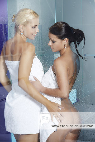 Zwei nackte junge Frauen trocknen sich gegenseitig mit Handtüchern hinter Glasabtrennung einer Duschkabine