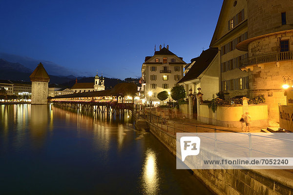 The lights of Chapel Bridge and the water tower are reflected in the water of the Reuss river  Lucerne  Switzerland  Europe