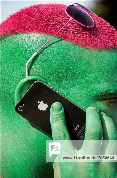 Contemporary lifestyle  man's face painted in green colour  man talking by mobile phone  taken during Lake Parade - LGBT Parade  Pride Parade  Geneva  Switzerland  Europe