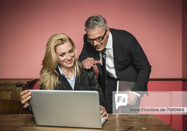 Businessman and woman working on laptop  smiling