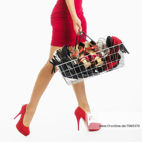 niedrig  Anschnitt  Studioaufnahme  Frau  tragen  Korb  Schuh  kaufen