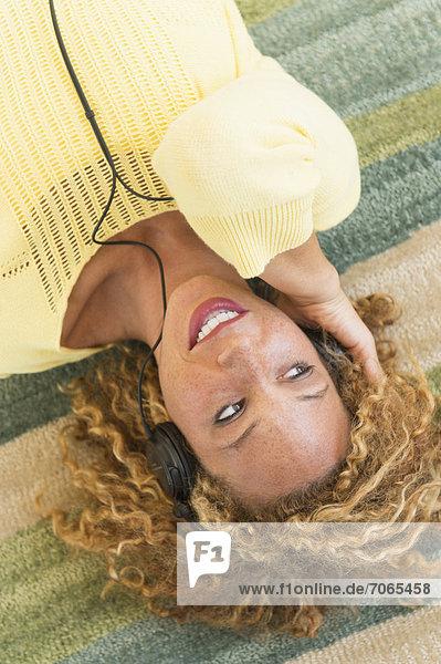 liegend  liegen  liegt  liegendes  liegender  liegende  daliegen  Frau  zuhören  Kopfhörer  Musik  Teppichboden  Teppich  Teppiche  jung