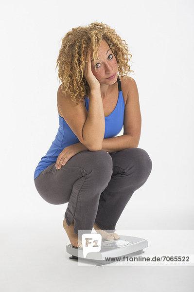 Waage - Messgerät  Studioaufnahme  hocken - Mensch  Portrait  Frau  Gewicht  jung