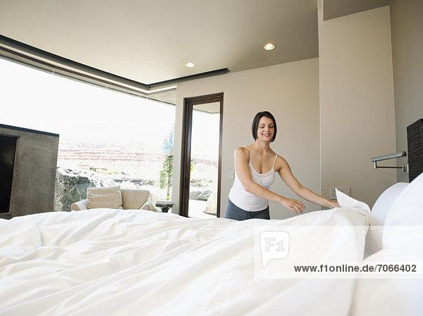 Junge Frau machen Bett
