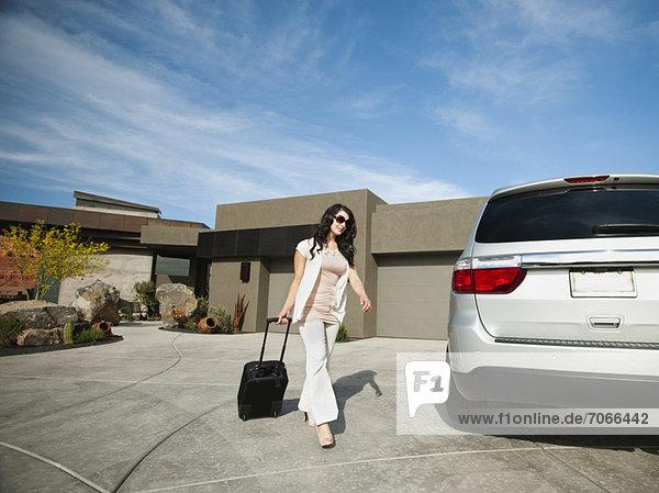 junge Frau junge Frauen gehen Auto Koffer