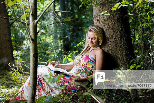 Junge Frau im Wald  beim Lesen