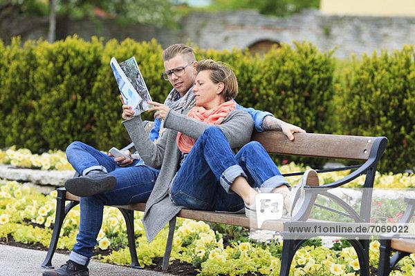 Mittlere erwachsene Frau  die dem Mann im Magazin etwas zeigt  während sie auf der Parkbank sitzt.