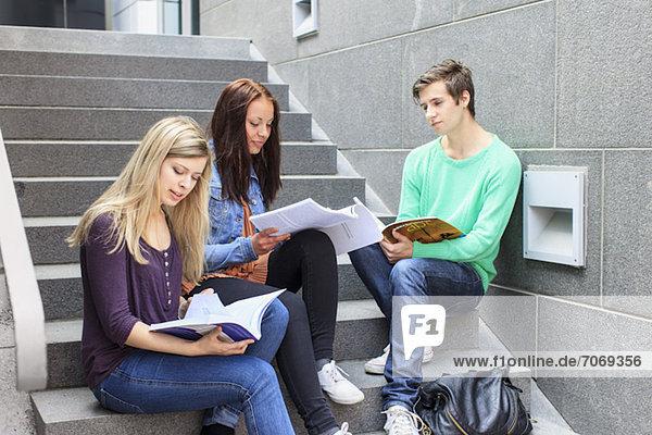 Junge Studenten studieren auf Stufen in der Universität