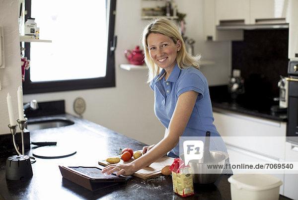 Mittlere erwachsene Frau mit Rezept auf digitalem Tisch und Zubereitung des Essens in der Küche