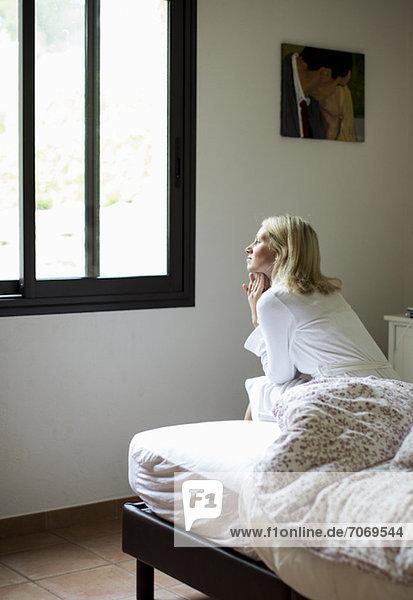 Nachdenkliche erwachsene Frau  die auf dem Bett sitzt und aus dem Fenster schaut.