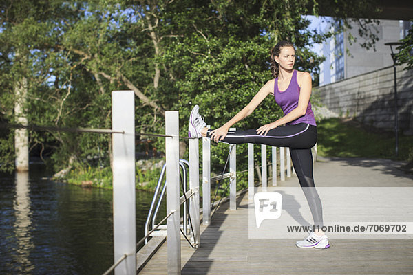 Seitenansicht einer jungen Frau  die ihr Bein am Zaun streckt.