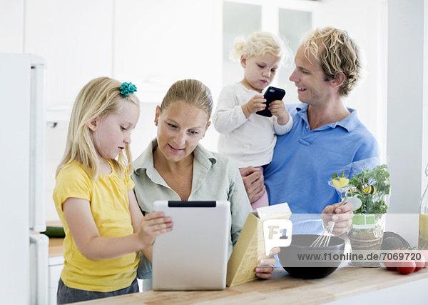 Familie mit digitaler Tablette für die Kuchenzubereitung in der Küche