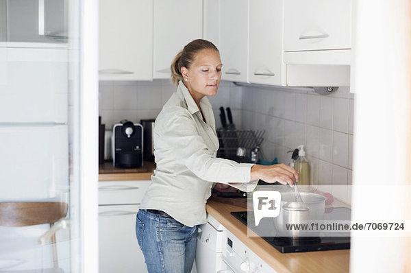 Mittlere erwachsene Frau bei der Zubereitung von Speisen in der Küche