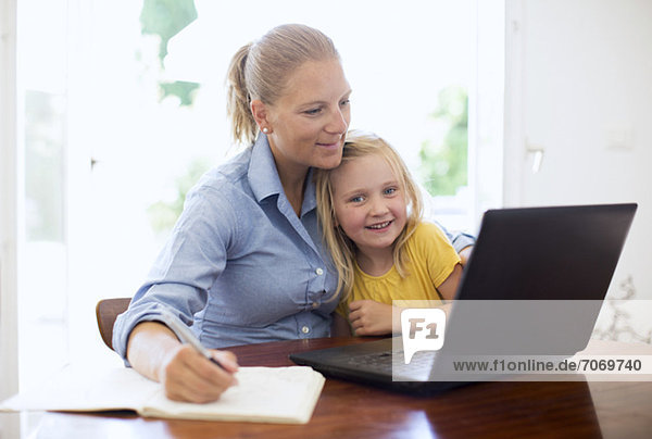 Mid adult woman using laptop while writing notes sitting with daughter at desk