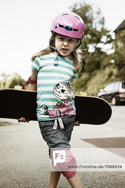 Porträt eines selbstbewussten Mädchens mit Skateboard im Freien