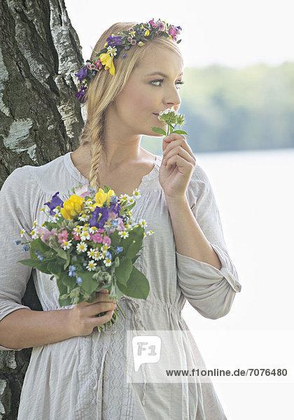 Junge Frau mit Sommerstrauß  riecht an Blume Junge Frau mit Sommerstrauß, riecht an Blume