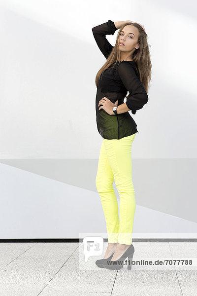 Junge Frau mit schwarzem Oberteil  leuchtgelber Hose und hohen schwarzen Schuhen