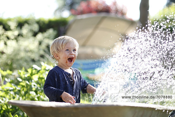 Young boy with his mouth smeared with chocolate playing with a garden hose and laughing