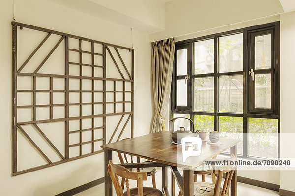 A Chinese style wooden table  with pottery teapot and cups. Chairs. A wooden frame decoration on the wall. Window. Living room in a house.