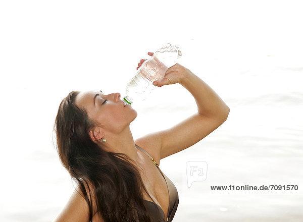 Junge Frau trinkt Wasser aus der Flasche