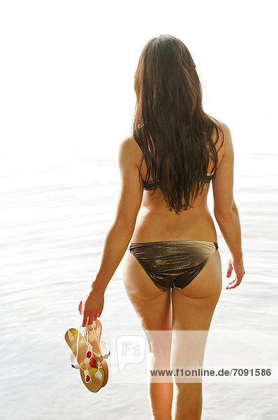Young woman holding flip flops in lake